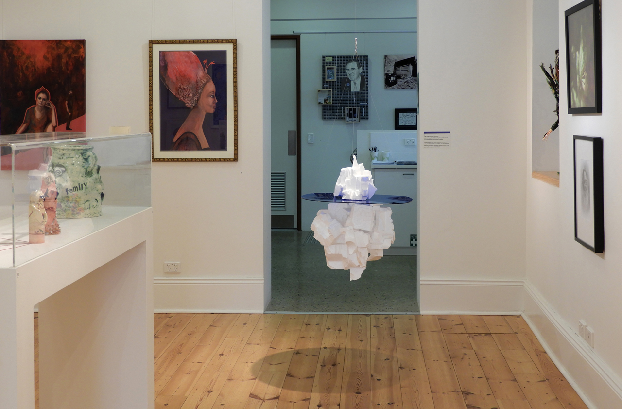 Shows Dan Monceaux's iceberg sculpture suspended from the ceiling in Gallery 1855